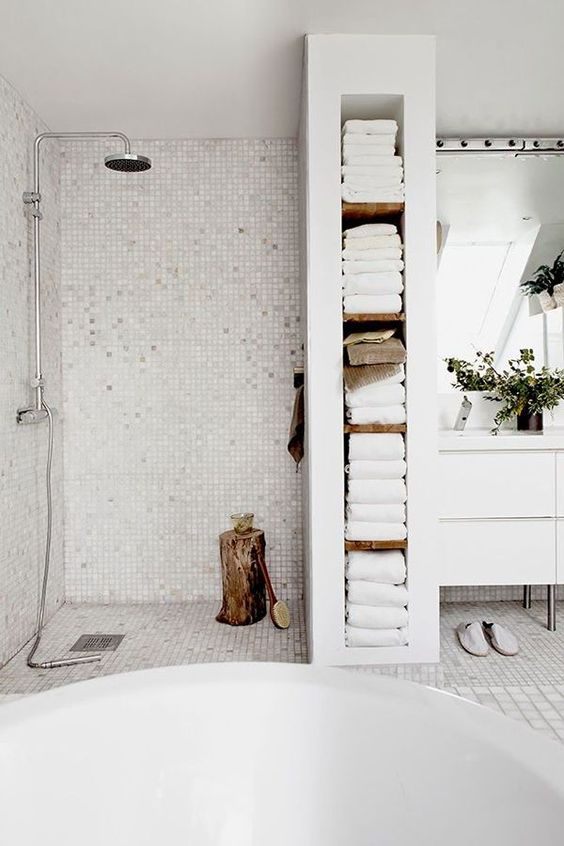 a built-in shelving unit separates the shower and the sink zone and is used for towels