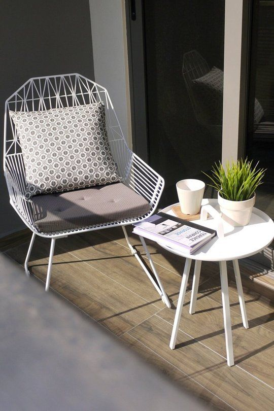 a comfy metal chair with cushions and pillows and a small coffee table