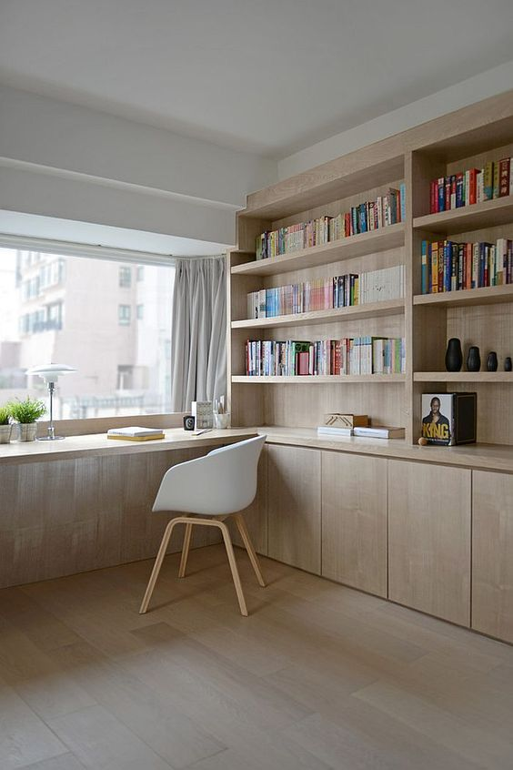 a minimalist home office with bookshelves and a windowsill as a desk