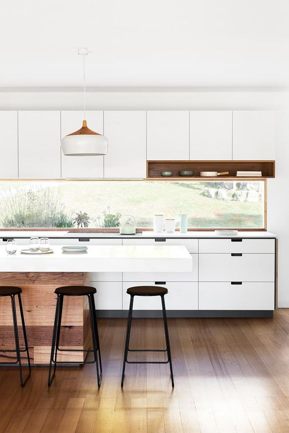 a modern white kitchen with metal stools and reclaimed wood is enlivened with a window backsplash
