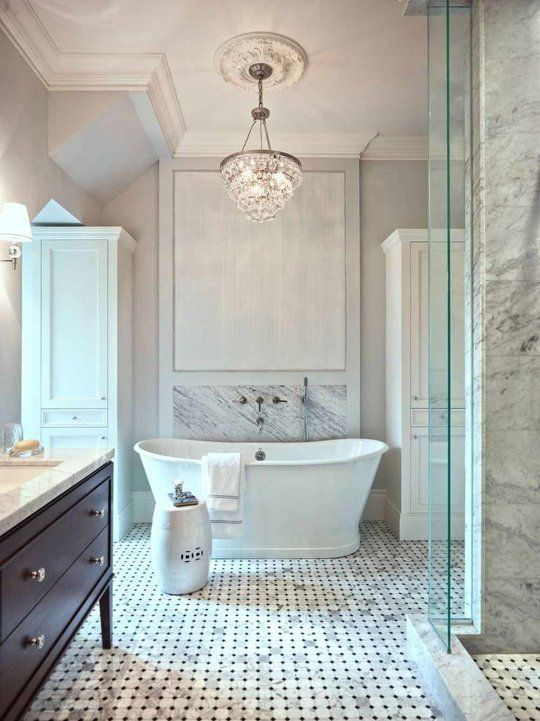 a refined marble bathroom with a crystal chandelier accentuated with a ceiling medallion