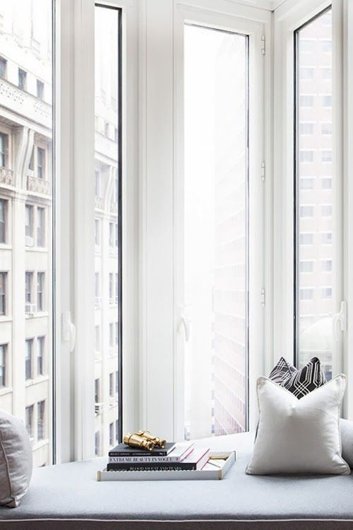 a small upholstered window sill reading nook with views of a big city