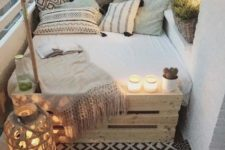 07 a square pallet bed, some cushions and pillows and a couple candle lanterns to enjoy sleeping outside