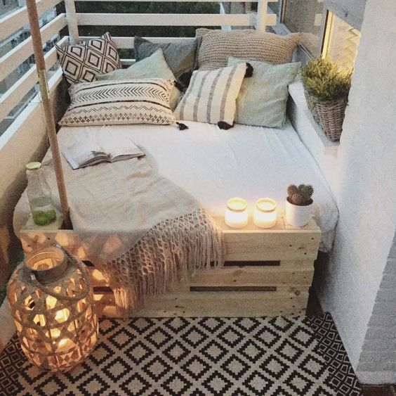 a square pallet bed, some cushions and pillows and a couple candle lanterns to enjoy sleeping outside