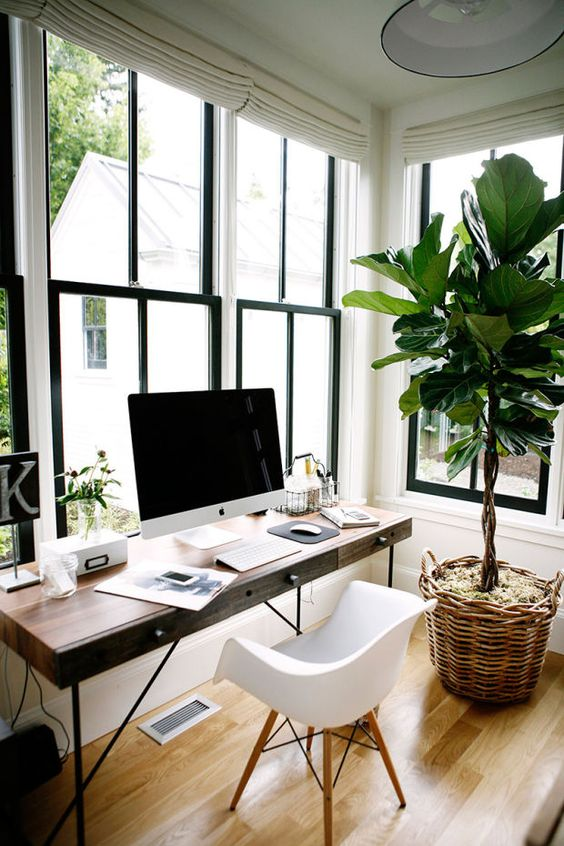 a wooden desk, a modern chair, black frame windows and a plant in a basket