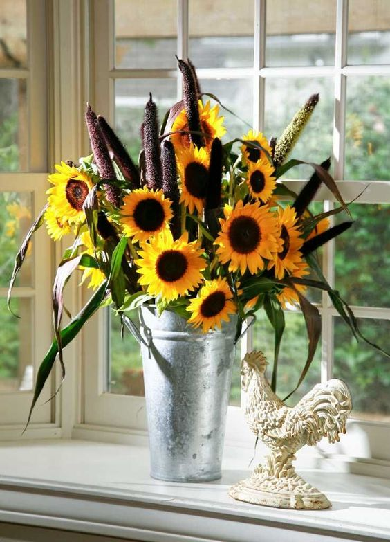 a bucket with sunflowers, grass and bulrush