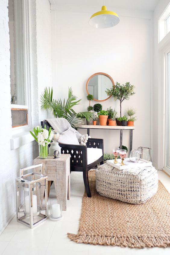 a dark stained chair with white cushions, a pouf and a jute rug for a cozy balcony