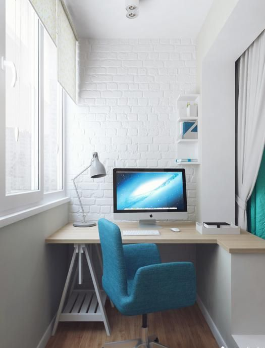 a modern white balcony with faux brick walls, a half-floating desk and a comfy blue chair