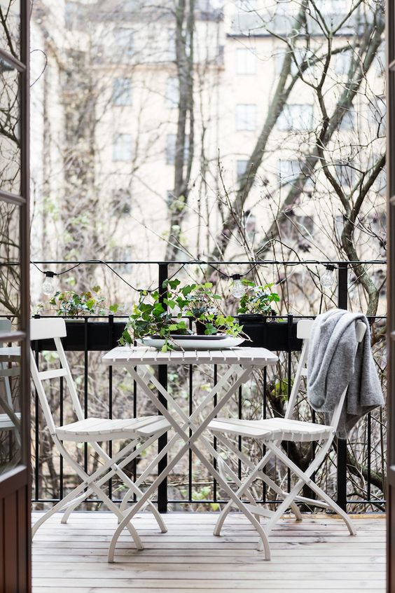 a white folding furniture set and black hanging planters with greenery for breakfast