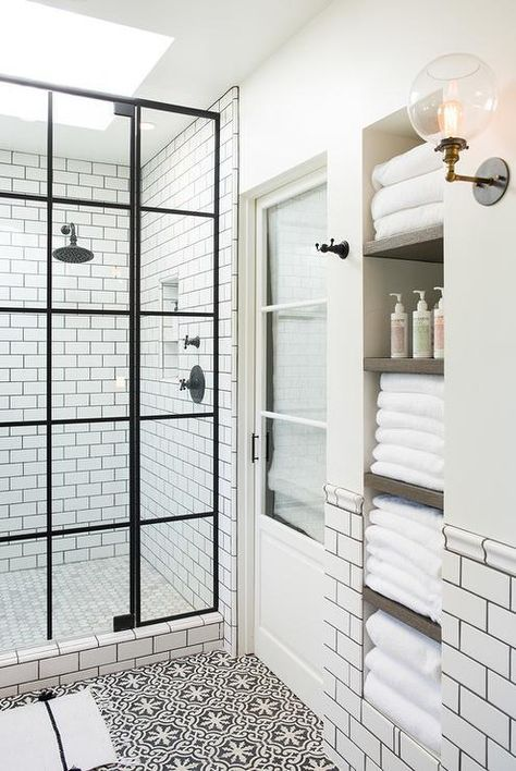 this white and black bathroom is made brighter with skylights over the shower