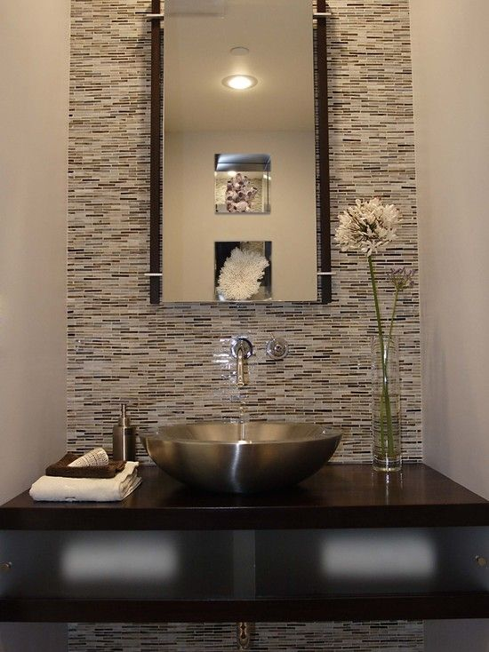 a dark powder room with a matte metal sink and a dark vanity