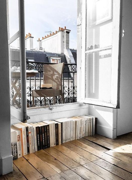 a wicker chair and a small table and books stacked right next to the window for comfy reading