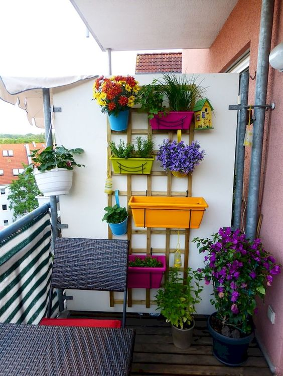 a wooden trellis attached to the wall and colorful planters on it