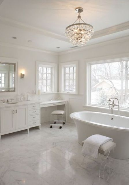 an all-white bathroom with marble, a free-standing bathtub and a glam chandelier
