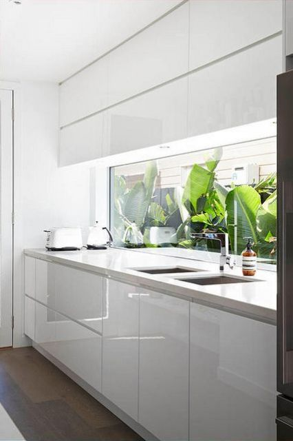 glossy finish kitchen cabinets and a window backsplash with tropical views for a contrast