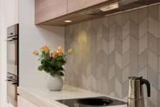 09 herringbone clad tiles in grey shades make the wooden kitchen look modern