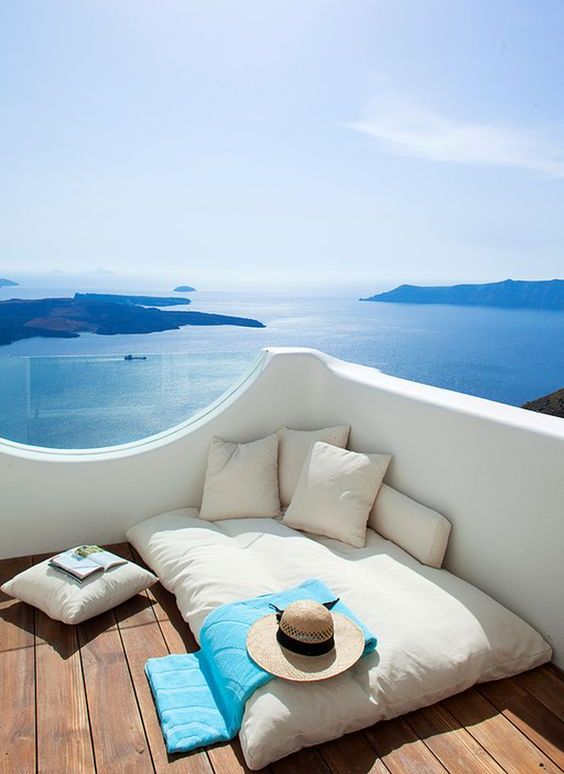 a balcony with a gorgeous sea view and a soft mattress and pillows to sleep