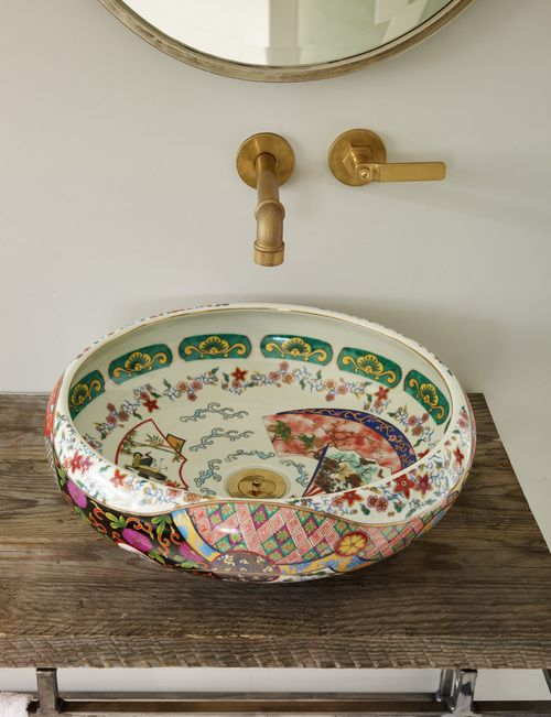 a bold painted porcelain bowl sink contrasts a rough wood stand