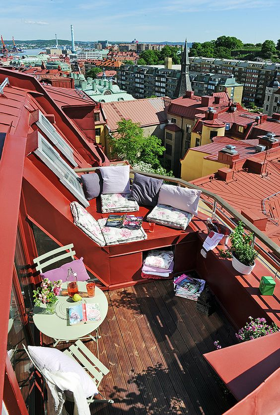 a red balcony with a window sill coming along the whole balcony saves space and you can sit on it