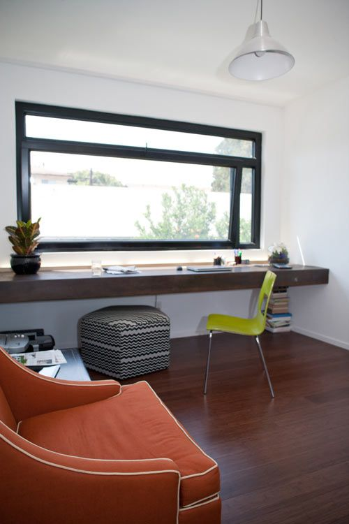 a thick dark wood windowsill turned into a stylish workspace by the black framed window