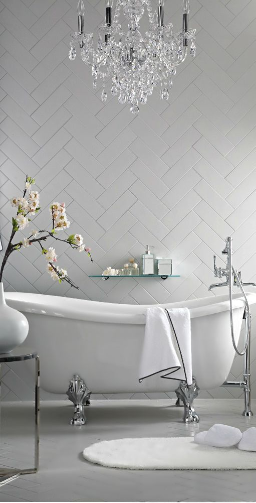 beautiful white bathroom with herrignbone tiles, a refined bathtub and a crystal chandelier