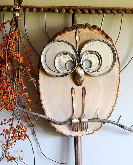 a fun kitchen art with forks, tin lids and a spoon and a wood slice