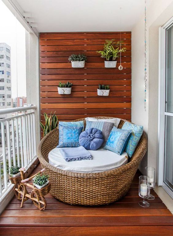 a wood wall and deck with planters, a wicker chair with pillows and a cushion