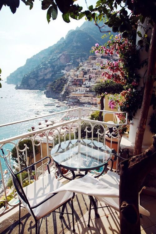 a glass table and forged chairs for a tiny breakfast nook in Positano