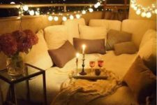 13 a mattress on the balcony covered with pillows, some candles and lights over it for a romantic date