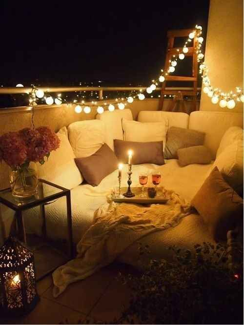a mattress on the balcony covered with pillows, some candles and lights over it for a romantic date