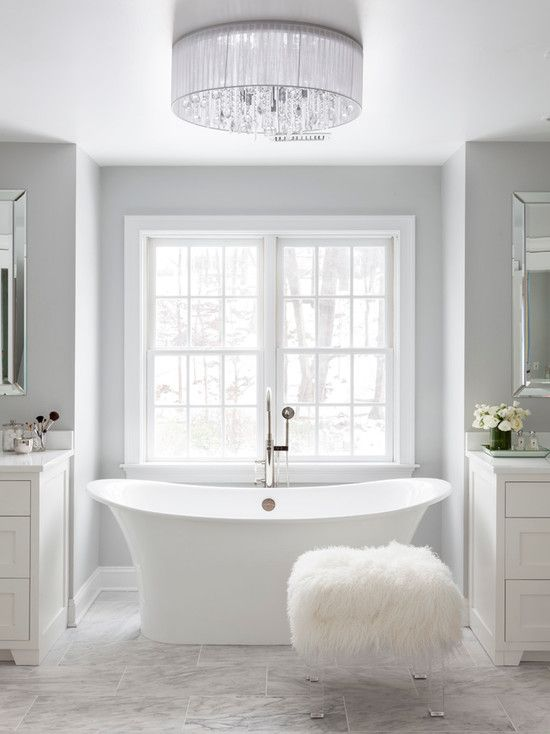 a relaxed white bathroom is made gorgeous with a modern crystal chandelier and a fur covered stool