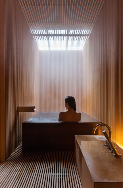 Japanese styled bathroom with skylights over the bathtub for a spa feel