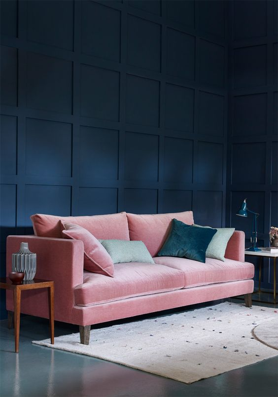 a navy room is softened with a pink velvet sofa