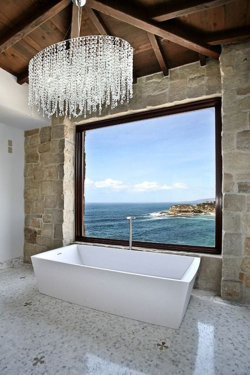 a rustic bathroom with a gorgeous view and an oversized crystal chandelier - nothing else is needed