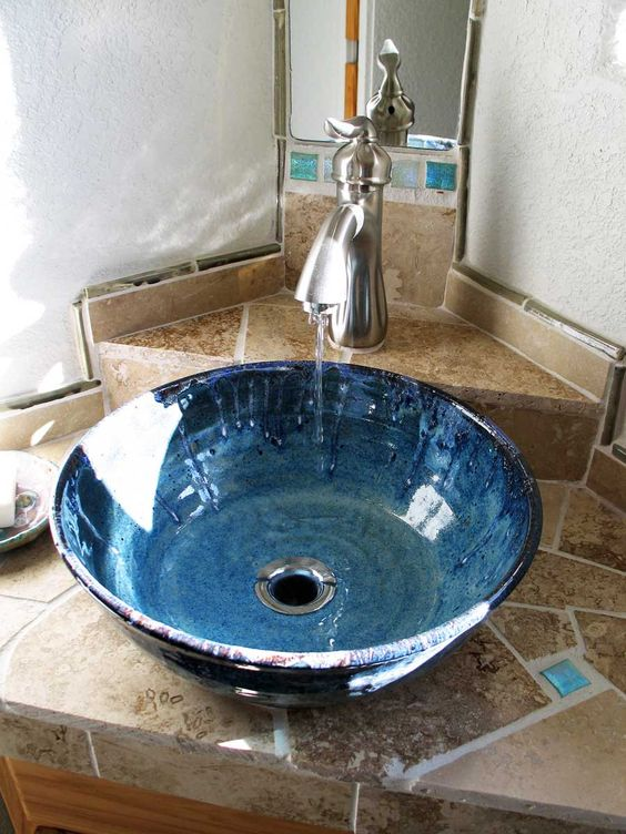 an ombre blue potter sink with a vintage faucet looks very coastal-inspired