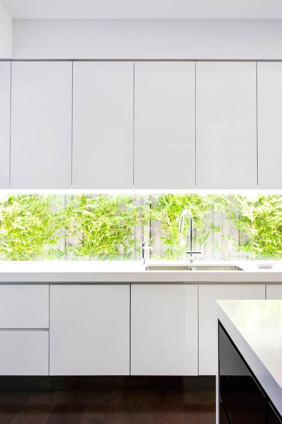 minimalist white sleek kitchen cabinets and a long narrow backsplash with the views on the living wall