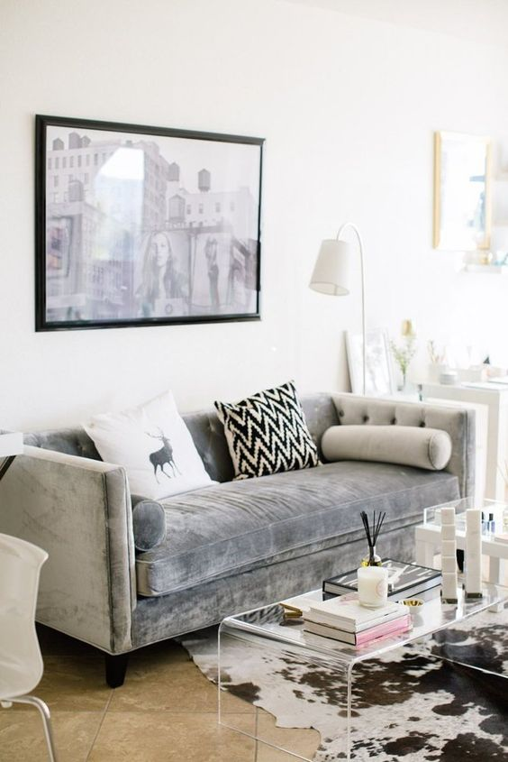 a modern living room is added a textural touch with an acrylic table and a grey velvet sofa