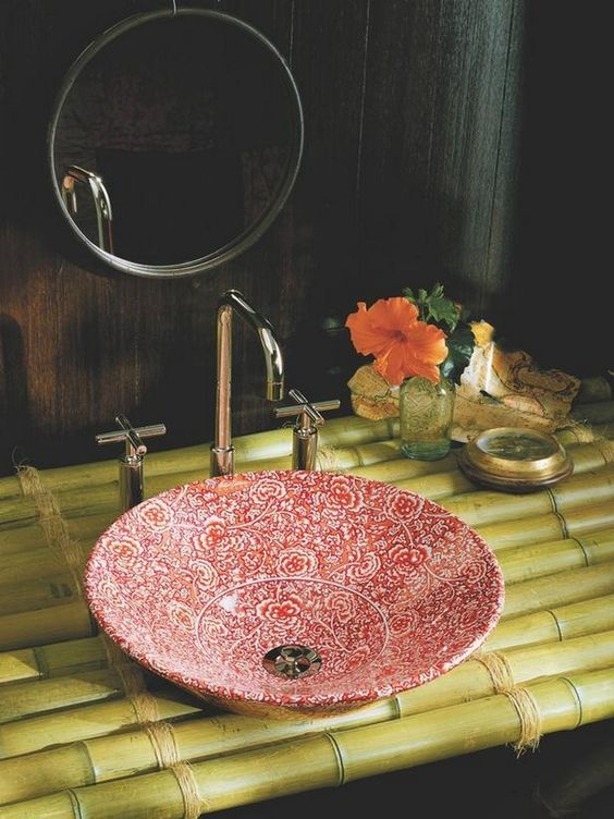 a red and white painted bowl sink and a bamboo stand creates a fantastic look
