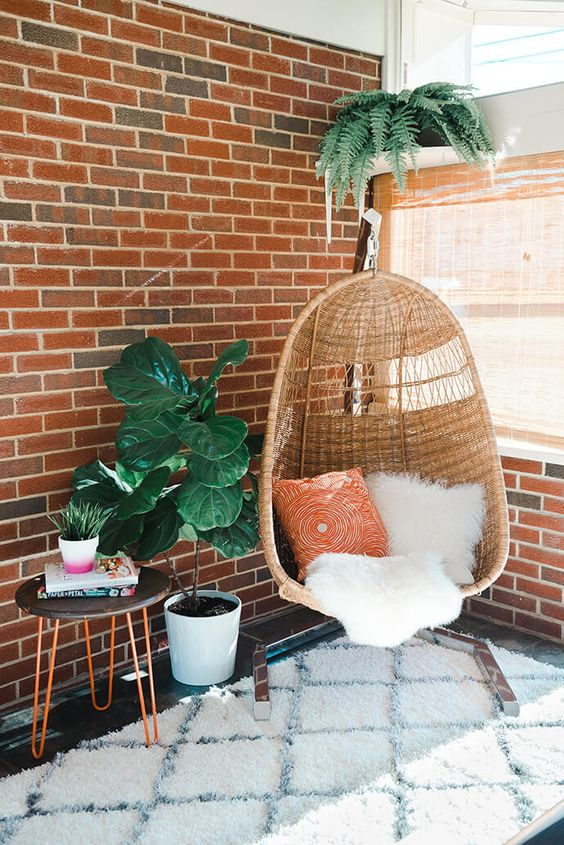 a wicker chair, a cozy rug and a potted plant for cozy reading