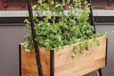 15 a wooden planter with a shelf to store different things and a trellis on top for growing vines