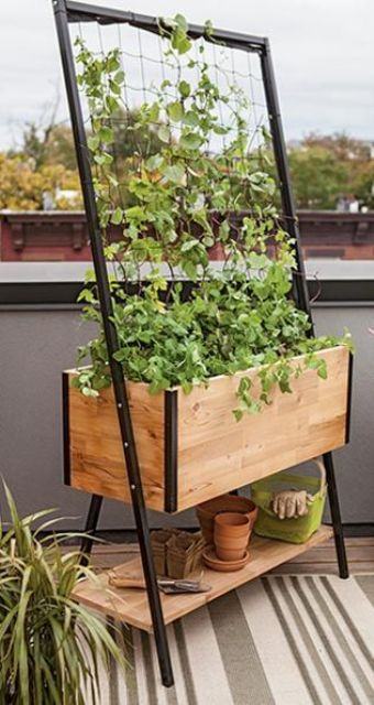 a wooden planter with a shelf to store different things and a trellis on top for growing vines