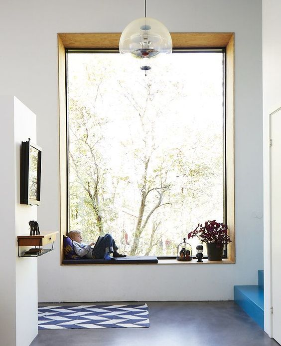 an double height window with a low window sill that features a kid's daybed