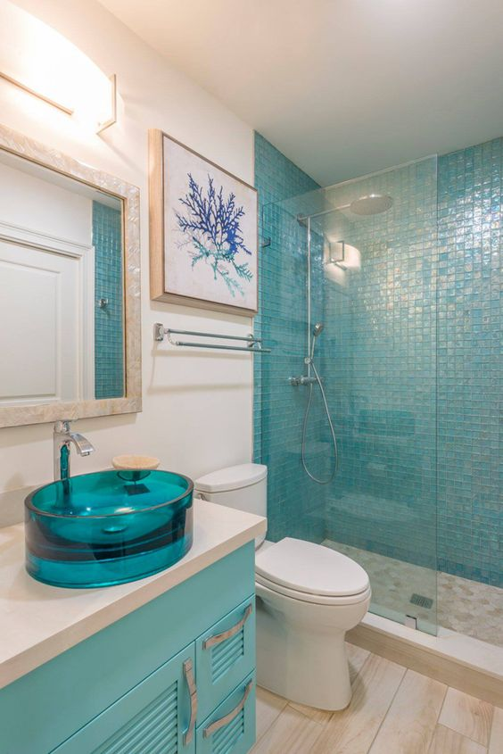 turquoise glass sink makes a colorful statement in the coastal bathroom