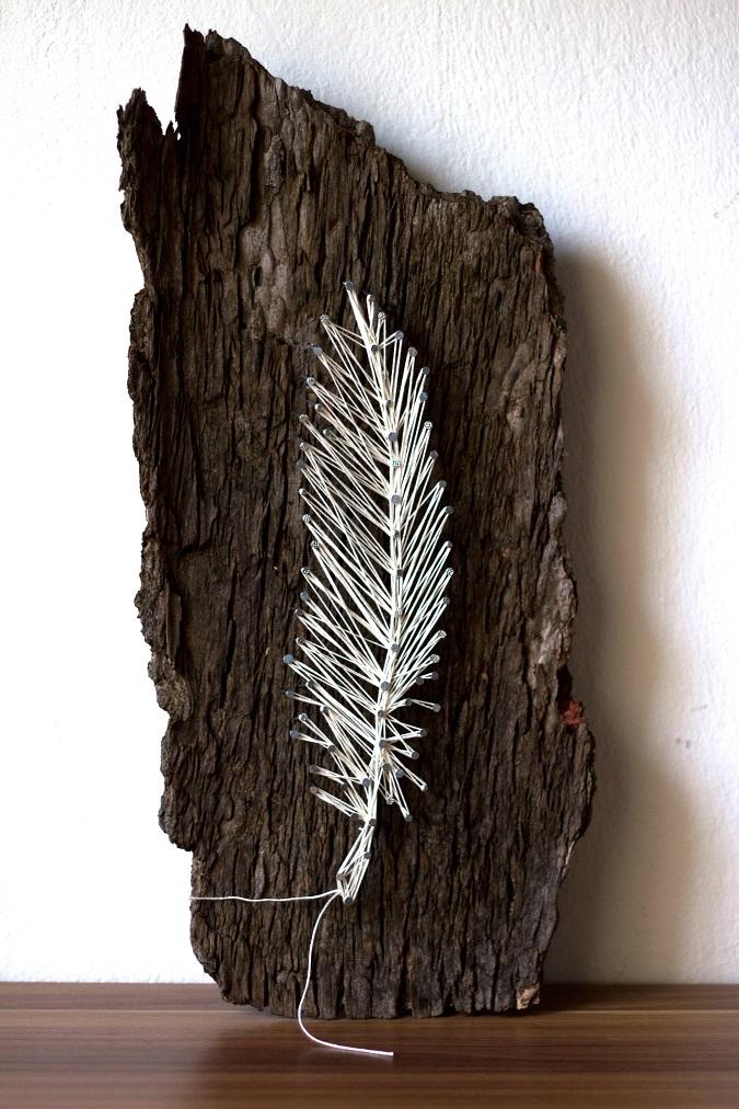 DIY feather art piece on dark wood (via www.green-bird.at)