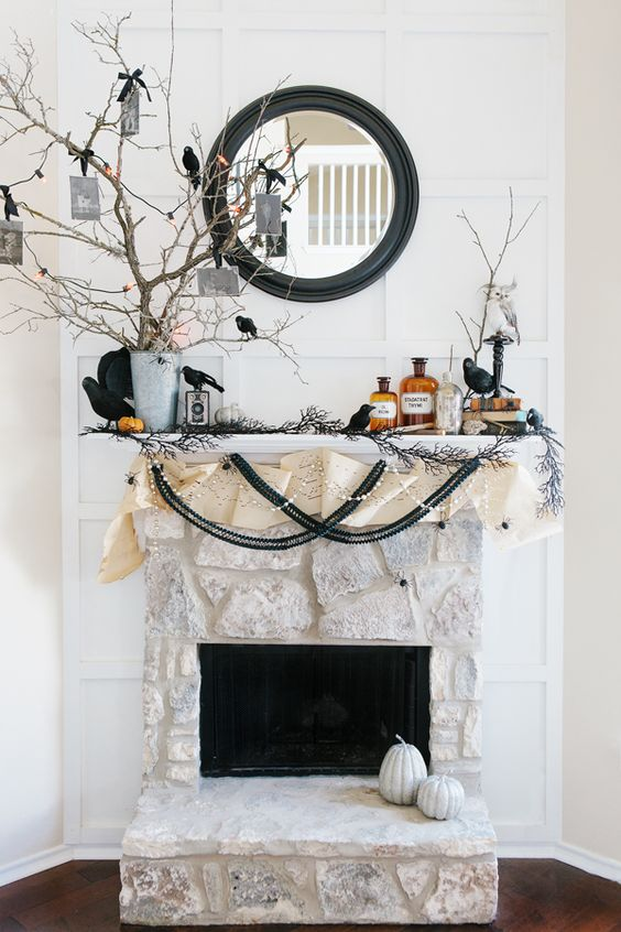 Halloween mantel with branches in a bucket with favors, banners, faux birds and a black framed mirror