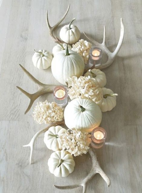a beautiful neutral centerpiece with why hydrangeas, antlers, candles and pumpkins