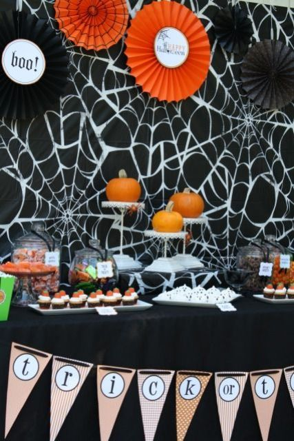 a black and orange dessert table with paper fans, spider webs, banners and orange pumpkins
