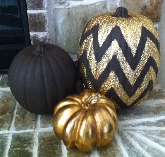 a chic pumpkin trio of a matte black, glossy gold and a chevron black and gold glitter pumpkin