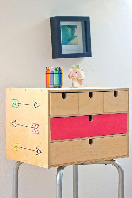 a colorful Ikea Moppe sideboard with arrows and a pink drawer