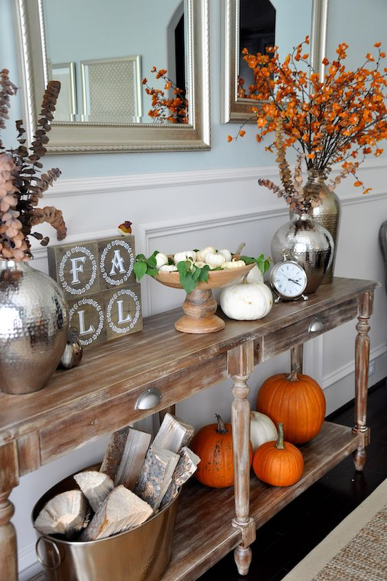a rustic console table with white and orange pumpkins on display, a fall sign, firewood in a bathtub